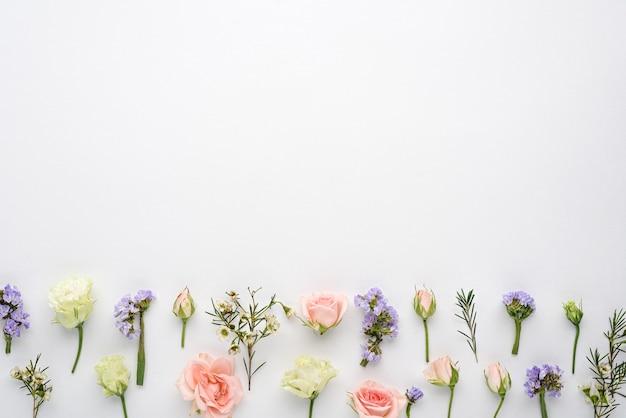 Composizione di fiori di boccioli di rosa, eustoma, infiorescenze di limonium su bianco