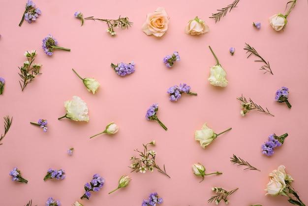 Composizione di fiori, rose, eustoma, limonium su sfondo rosa pastello, piatto laico, vista dall'alto, concetto di primavera