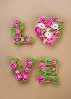 Composizione di fiori con lettere di volume amore parola con muschio stabilizzato e rose su sfondo di carta artigianale. vista dall'alto, piatto.