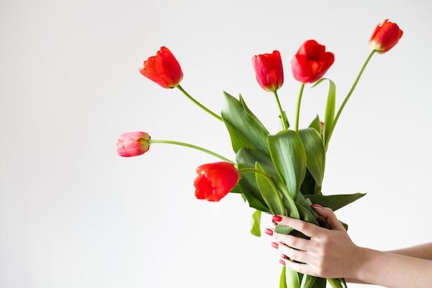Consegna dei fiori. fiorista che tiene un mazzo di tulipani rossi.