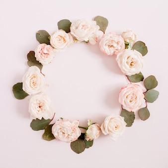 Cornice floreale composta da rose beige, rami di eucalipto su rosa pastello pallido.
