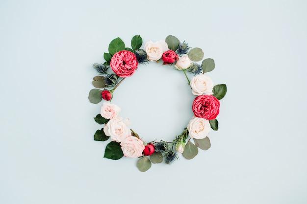 Corona di fiori cornice fatta di rose beige e rosse, rami di eucalipto su azzurro pastello pallido
