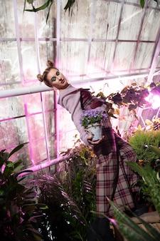 Giardino floreale. bella donna magnetica che mostra un vaso di fiori mentre sta in piedi nel giardino fiorito