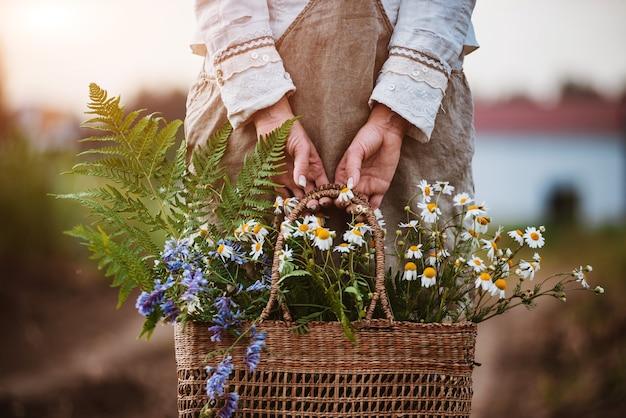 La fioraia trasporta cesto di vimini con fiori di campo al tramonto nei raggi