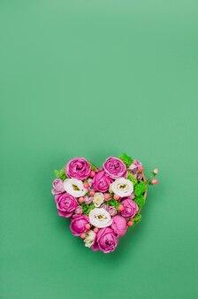Scatola a forma di cuore fiore su sfondo verde con uno spazio vuoto per il testo. vista dall'alto, piatto.