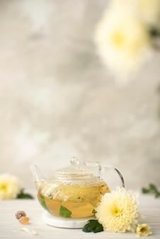 Tisana di fiori con petali di crisantemo in una teiera di vetro, primo piano