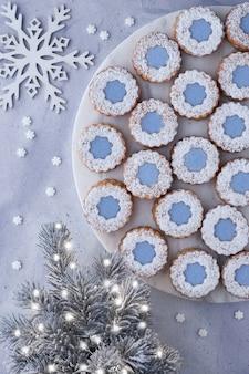 I biscotti di linzer del fiore con glassa blu sul bordo bianco di marmore hanno messo sopra la superficie leggera dell'inverno con l'albero di natale