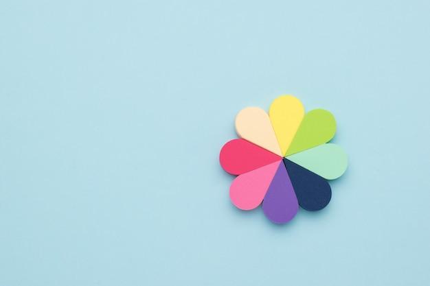 Un fiore fatto di spugne multicolori cosmetiche su una superficie blu