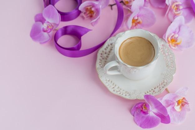 Composizione ambientale del fiore sulla vista superiore della superficie rosa-chiaro. tazza di caffè e fiori di orchidea perple. concetto di umore del caffè