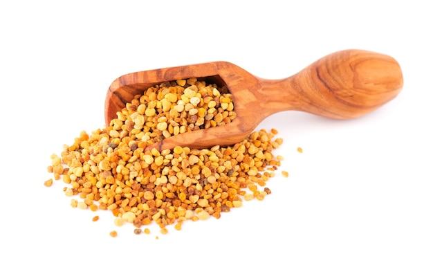 Chicchi di polline di fiori in cucchiaio di legno, isolato su bianco. pila di polline d'api o perga.