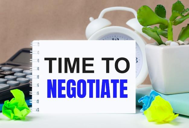 Fiore in vaso, calcolatrice, sveglia bianca, pezzi di carta multicolori e un quaderno bianco con il testo time to negotiate sul desktop.
