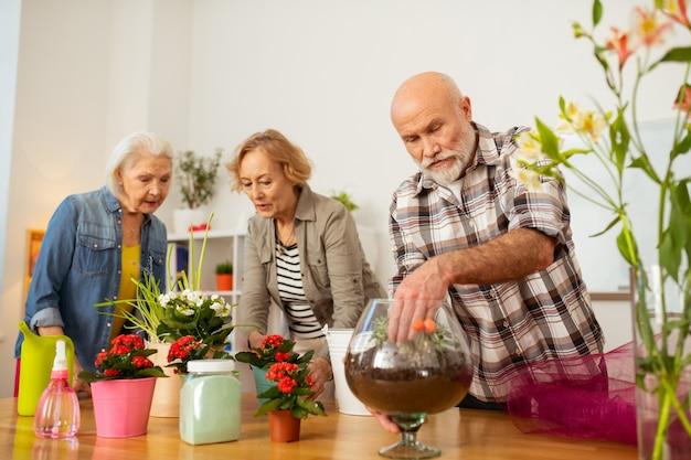 Invasatura di fiori. piacevole uomo simpatico che mette la mano nel vaso mentre pianta un fiore