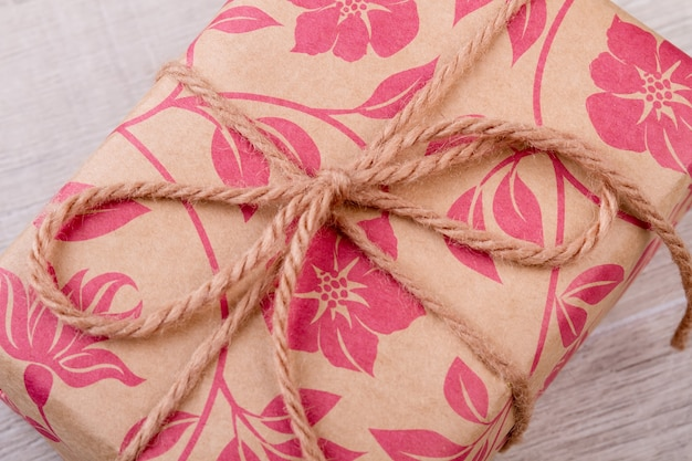 Involucro e corda con stampa floreale. pacchetto su fondo di legno. idee per incartare i regali. sii grato per i regali.