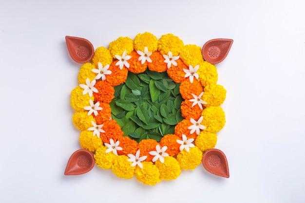 Flower rangoli per diwali festival realizzati con calendula e foglia e lampada a olio su sfondo bianco