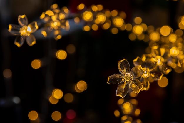 Luci di natale a forma di fiore con luci sfocate sullo sfondo