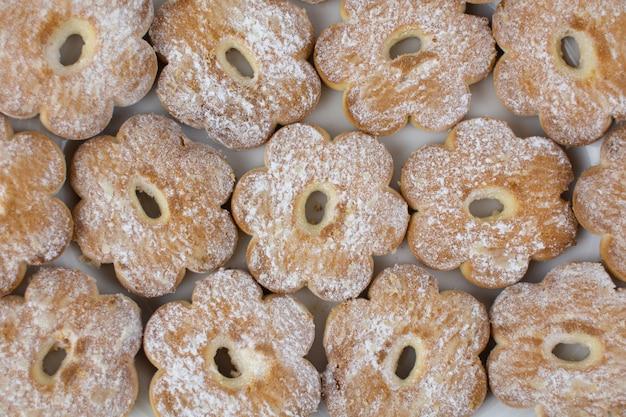 Biscotti a forma di fiore su sfondo di zucchero a velo Foto Premium