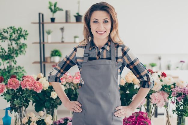 Proprietario del negozio di fiori in posa circondato da fiori