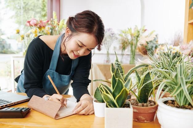 Proprietario del negozio di fiori che scrive in pianificatore
