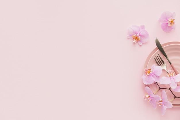 Composizione ambientale di impostazioni di fiori e tavoli su sfondo rosa chiaro