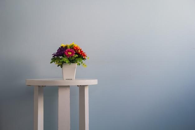 Fiore sul tavolo muro bianco sfondo blu