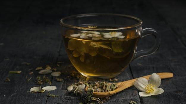 Tè ai fiori in una tazza di vetro e un cucchiaio di legno su un tavolo nero.