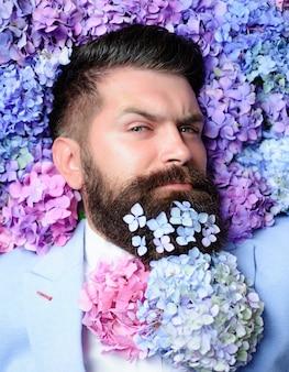 Fiori nella barba. uomo barbuto con una barba decorata per le vacanze di primavera.