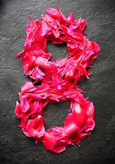 Fiori su sfondo nero. numero otto da petali di peonie. saluto per la giornata internazionale della donna. idea per annuncio o invito.