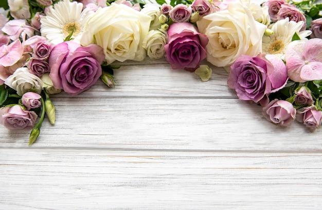 Composizione di fiori. bordo di fiori rosa su fondo di legno bianco. appartamento laico, vista dall'alto, copia dello spazio