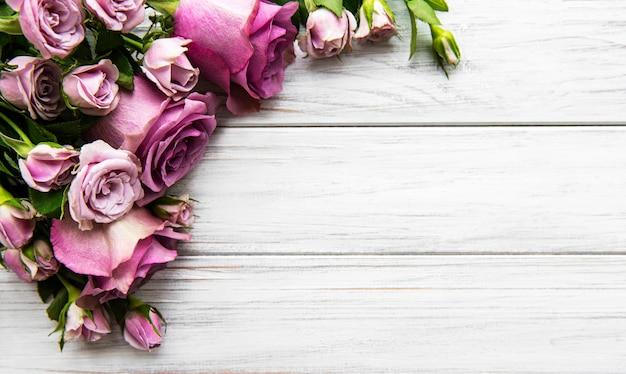 Composizione di fiori. cornice fatta di fiori di rosa rosa su fondo di legno bianco. appartamento laico, vista dall'alto, copia dello spazio