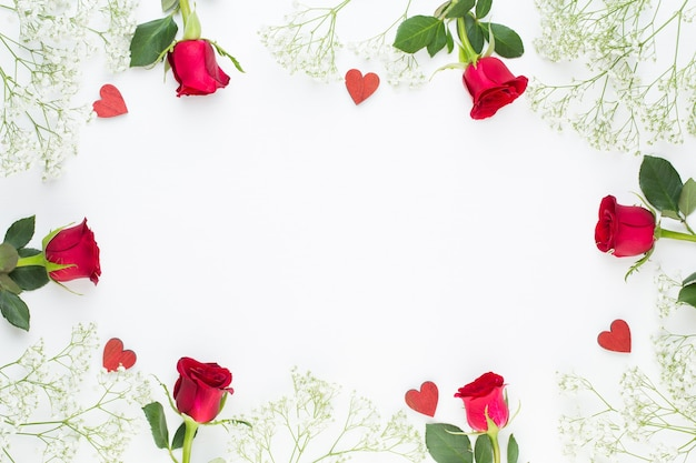 Composizione di fiori. cornice fatta di rosa rossa su sfondo bianco. appartamento laico, vista dall'alto, copia dello spazio.