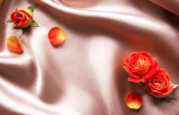 Composizione di fiori cornice fatta di rose rosse e foglie su sfondo di seta beige space