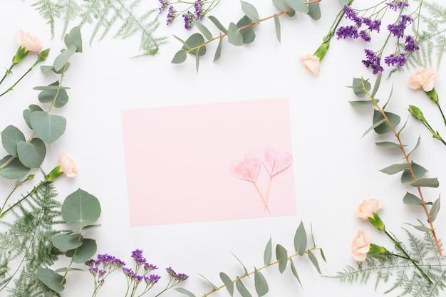 Composizione di fiori. carta in bianco, fiori di garofano, rami di eucalipto su pastello