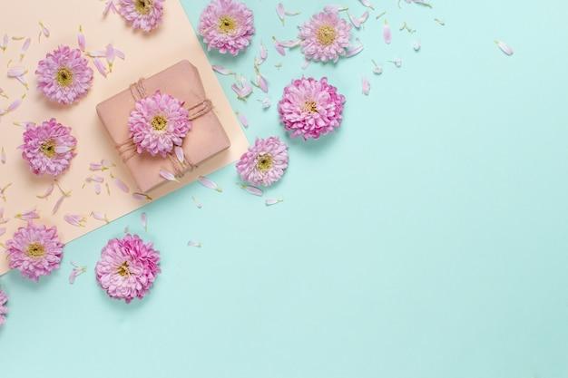 Composizione di fiori con confezione regalo su fondo pastello
