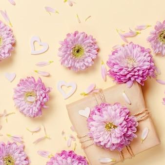 Composizione di fiori con cuori e confezione regalo su uno sfondo giallo pastello
