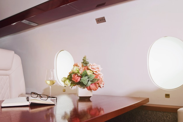 Fiori, diario, bicchiere di vino sul tavolo da lavoro di interni di lusso in jet privato. aereo d'affari moderno e confortevole con decorazioni. concetto di qualità del servizio passeggeri nell'industria aeronautica, al massimo