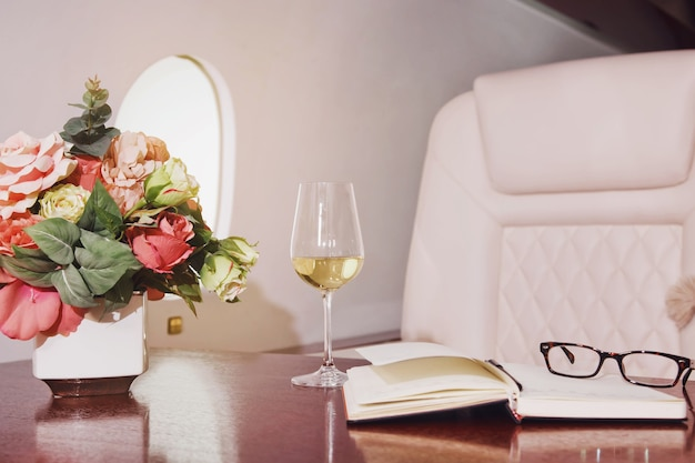 Fiori, diario, bicchiere di vino sul tavolo da lavoro di interni di lusso in jet privato