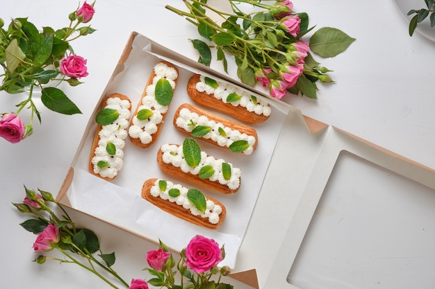 Fiori e bignè decorati con crema e menta su un tavolo bianco. dessert per un appuntamento romantico. torte per le feste.