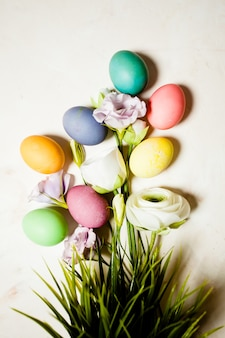 Fiori e uova su sfondo di marmo rosa, copia spazio per gli auguri di pasqua
