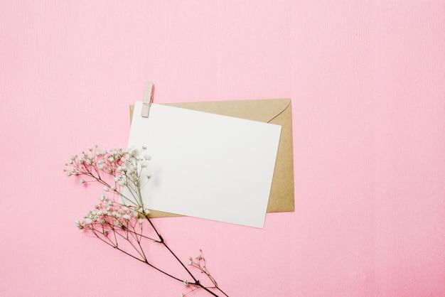 Fiori, busta e biglietto bianco. vista dall'alto