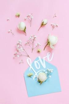 Fiori, busta e parola amore su una vista dall'alto di sfondo rosa chiaro