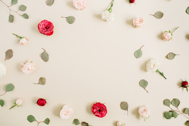 Cornice di fiori fatta di rose beige e rosse, foglia di eucalipto su fondo beige pastello pallido. disposizione piatta, vista dall'alto