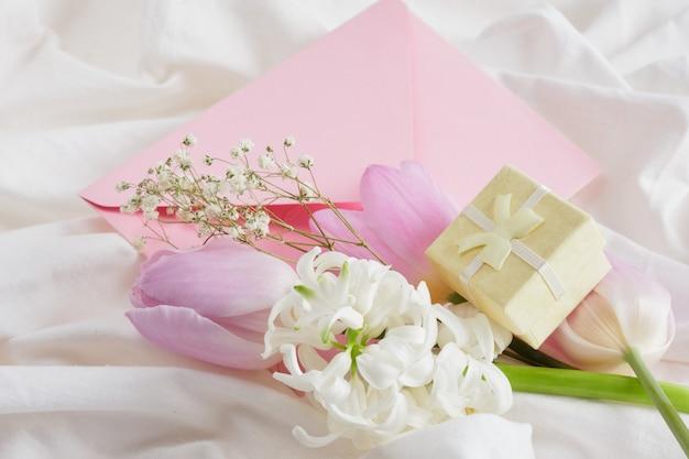 Fiori scatole regalo busta rosa sul letto regalo per donna concept