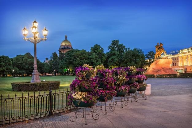Fiori e una lanterna sulla piazza del senato di san pietroburgo con il monumento a pietro il grande e la cattedrale di sant'isacco a distanza in una notte d'estate