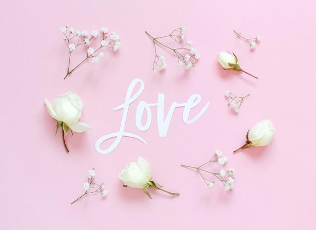 Fiori e scritte love su uno sfondo rosa chiaro vista dall'alto