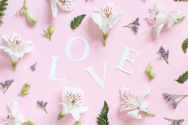 Fiori nad parola amore su una vista dall'alto di sfondo rosa chiaro