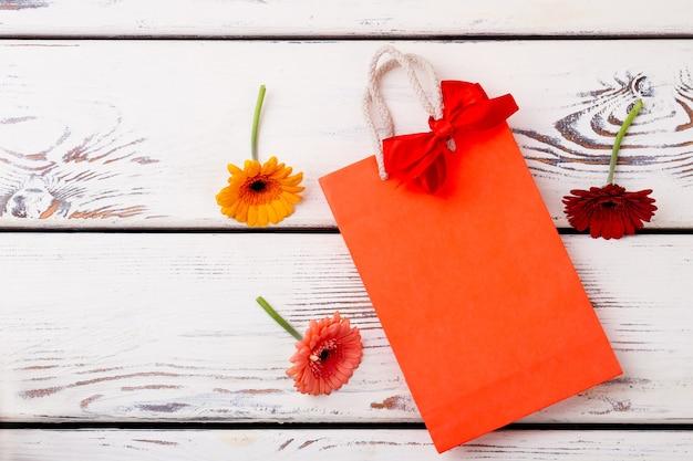 Fiori vicino a borsa con gerbere a fiocco e sacchetto su pacchetto di carta di legno per il regalo