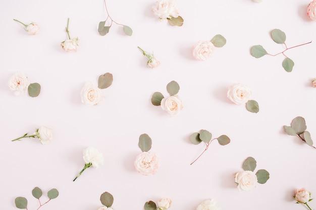 Struttura del modello di fiori fatta di rose beige, rami di eucalipto su sfondo rosa pastello pallido. disposizione piatta, vista dall'alto