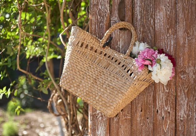 Fiori di peonie rosa rosse e bianche in cesto di vimini su tavola di legno su sfondo di legno