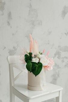 Fiori in una lussuosa confezione regalo rotonda. un bouquet di fiori rosa e bianchi in una scatola di carta. la disposizione delle cappelliere con fiori con copia gratuita dello spazio per il testo. l'interno è decorato in colori pastello.