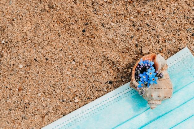 Fiori in conchiglia e maschera medica su una sabbia.